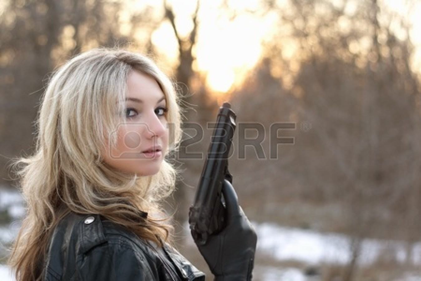 13320800-provocative-young-woman-holding-a-gun-in-winter-forest.jpg
