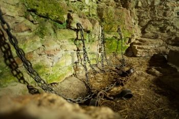 22331794-castle-dungeon-prison-with-chains-chain-and-moss-on-stone-walls.jpg