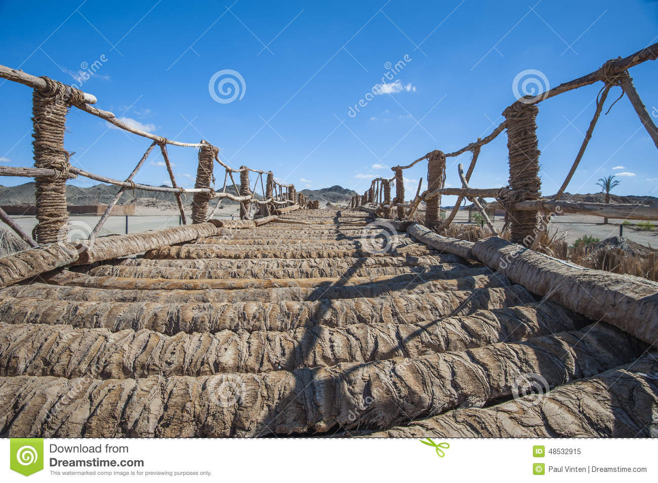 wooden-rope-bridge-remote-desert-log-across-landscape-blue-sky-48532915.jpg