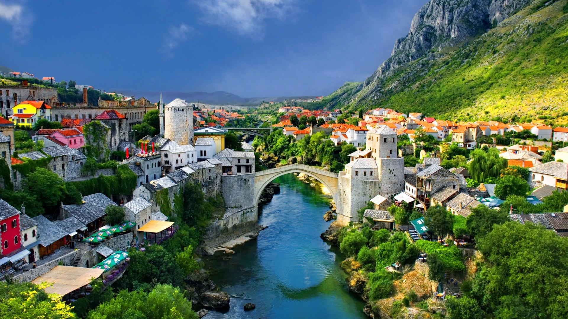 alpine_town_mountains_houses_bridge_river_trees_nature_landscape_63200_1920x1080.jpg