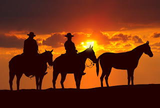 Cowboys against sunset