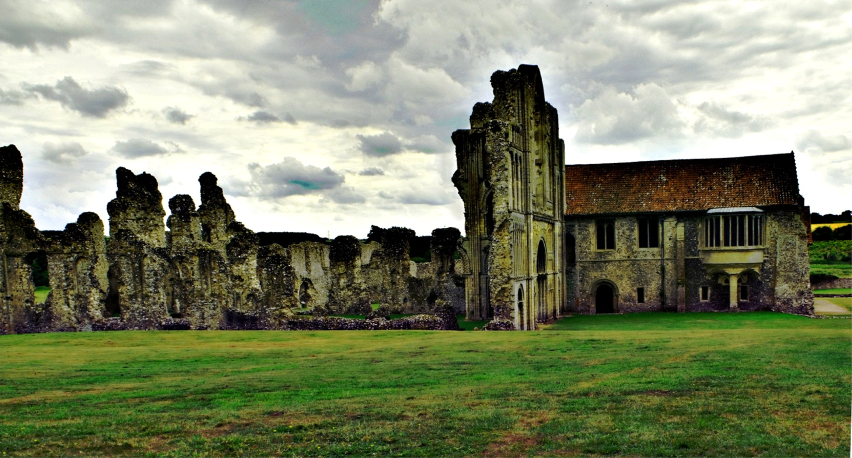 Castle acre priory sits ruined on a cloudy english day